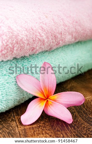 Clean Fresh Towel with Tropical Plumeria for spa and wellness concept focus pointed at the Tropical Plumeria using rule of third (RO3) and shallow DOF - stock photo