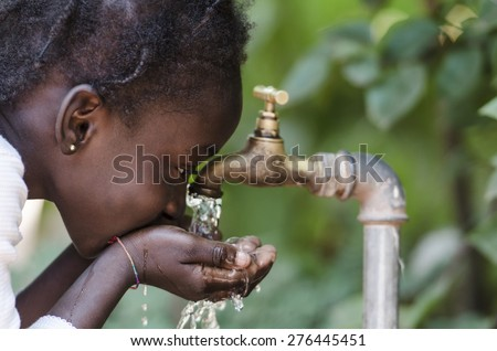 Clean Fresh Water Scarcity Symbol: Black Girl Drinking from Tap.  Young African girl drinking clean water from a tap. Hands with water pouring from a tap in the streets of the city Bamako, Mali. - stock photo