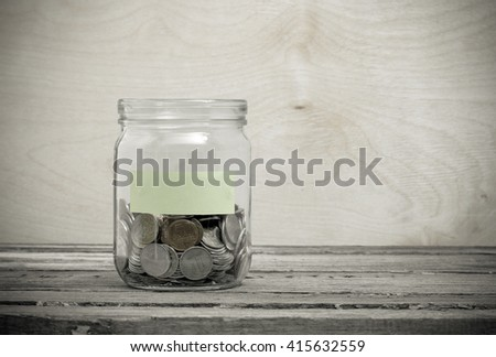 Clean label on a glass jar. Glass jar with coins. Financial concept on wooden background - stock photo