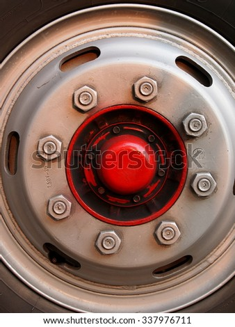 clean large wheel with eight lugs nuts on metallic iron wheel surface with red centre cap of a heavy duty vehicle transport bus and truck - stock photo