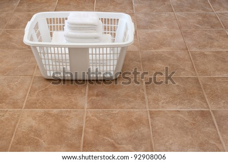 Clean laundry. White towels stacked in a laundry basket on ceramic floor. - stock photo