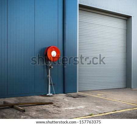 Clean, modern warehouse siding and roller door with red fire hose reel. - stock photo