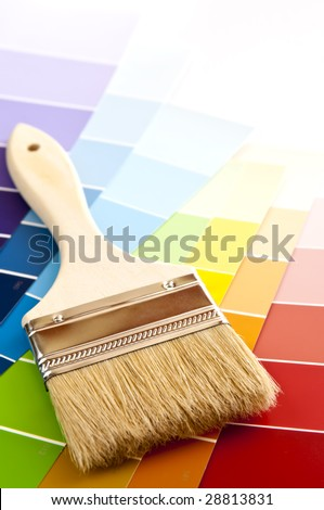 Clean paintbrush on rainbow of color card samples - stock photo