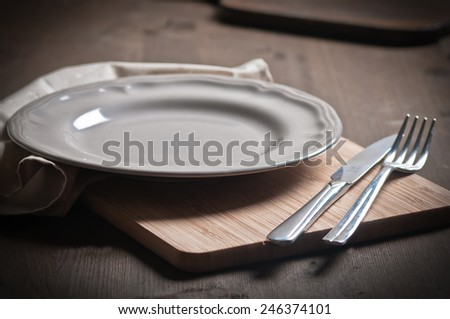Clean plate with knife, fork and napkin on wooden background. - stock photo
