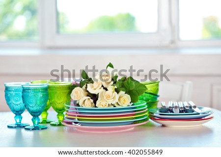 Clean plates, glasses and cutlery on white table - stock photo