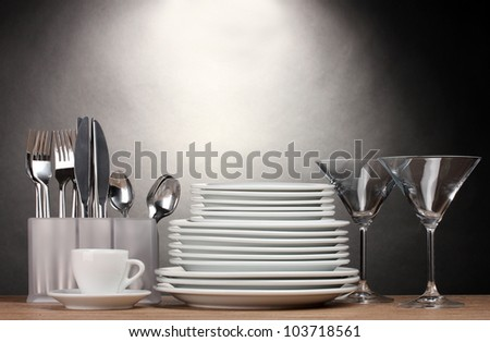 Clean plates, glasses, cup and cutlery on wooden table on grey background - stock photo