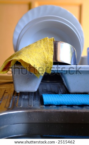 Clean plates, silver pot glass and other kitchen items in front of sink - stock photo