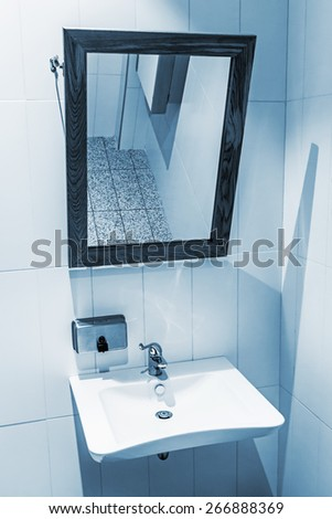 clean public washrooms interior. toning. Focus on the water faucets - stock photo