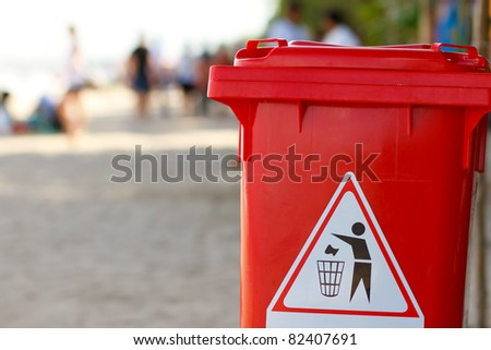 clean red plastic trash bin on the beach - stock photo