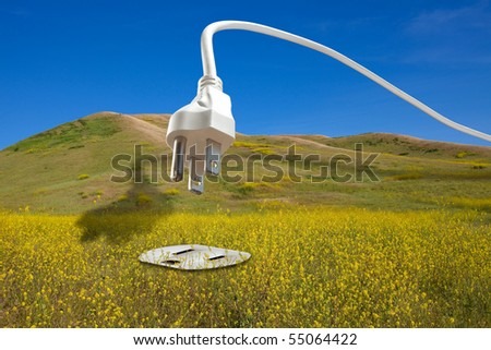 Clean renewable bio energy concept: large white power cord arching across a blue sky and diving down into an electrical plug set into a field of bio fuel mustard crops. - stock photo