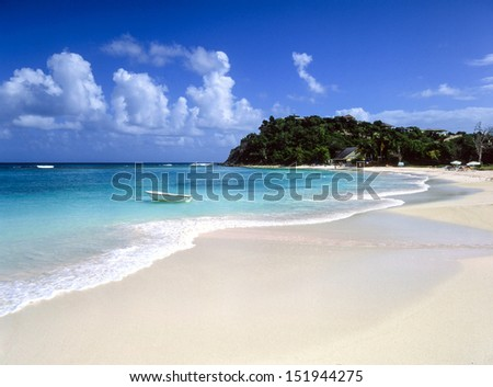 Clean sandy Caribbean beach and calm turquoise sea  - stock photo