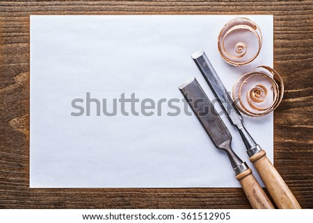 Clean sheet of paper wooden shavings flat chisels construction concept.