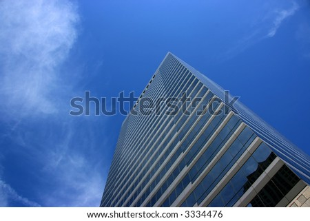 Clean skyscraper against a blue sky with some clouds. Wide angle view from below