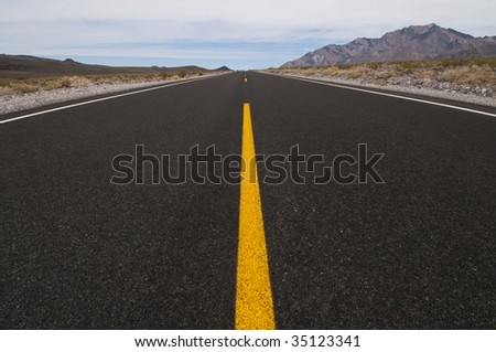 clean straight road through desert vanishing into distance - stock photo