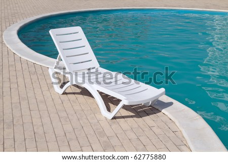 clean swimming pool and empty resting chair - stock photo
