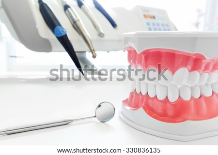 Clean teeth denture, dental jaw model, mirror and dentistry instruments in dentist's office.  - stock photo