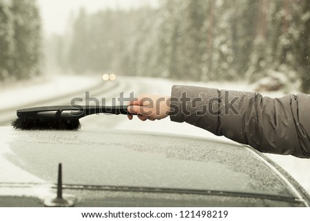 Clean the car out of the snow in snow storm on the road - stock photo
