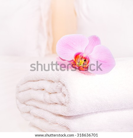 clean towel with orchid on the bed - stock photo