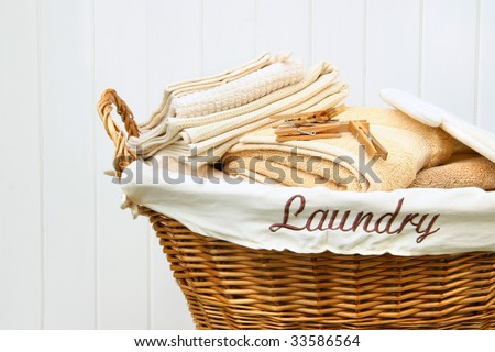 Clean towels in wicker basket with white wood background - stock photo
