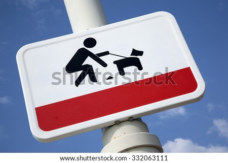Clean Up Dog Litter Sign against Blue Sky Background - stock photo