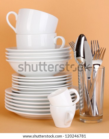 Clean white dishes on beige background - stock photo