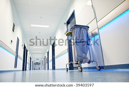 clean white long hospital corridor with blue leading lights - stock photo