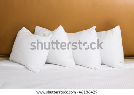Clean white pillows and sheet on bed - stock photo