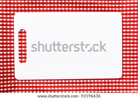 Clean White Plastic Cutting Board isolated on red and white checkered background - stock photo