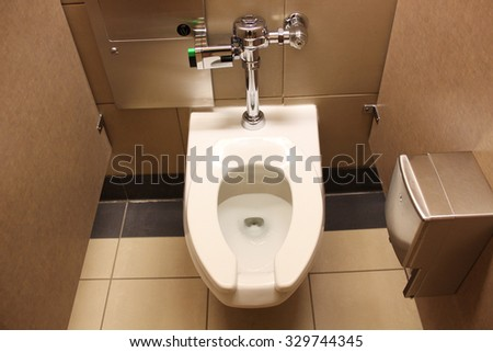 Clean white porcelain toilet with rails for handicap - stock photo