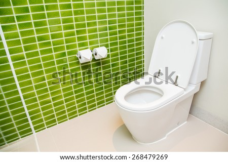 Clean, white toilet and paper rolls with Lime green mosaic tiles wall - stock photo