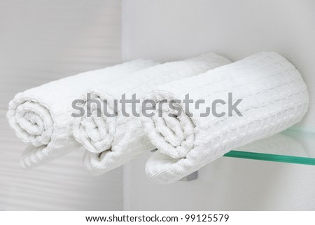 clean white towel on a glass shelf - stock photo