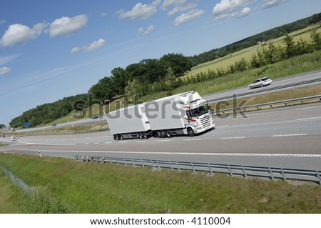 clean white truck on highway with field and forrest in background - stock photo