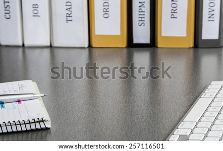 Clean working space with notepad, keyboard and folders. Clean and well ordered business working place with keyboard, notepad, colored folders. High contrast applied to highlight reflections of folders - stock photo