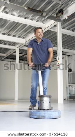 Cleaner polishing office floor - stock photo