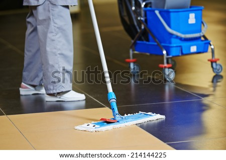 cleaner with mop and uniform cleaning hall floor of public business building - stock photo