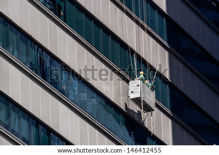 Cleaners cleaning the windows of a skyscraper in Singapore - stock photo