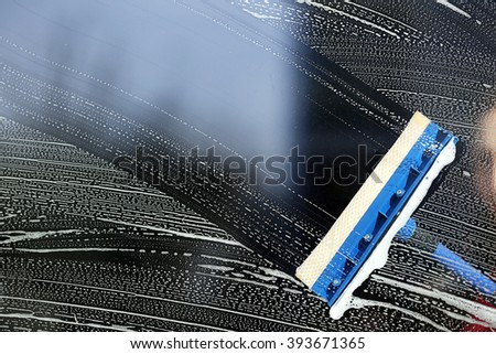 Cleaning a glass with a squeegee, close up - stock photo