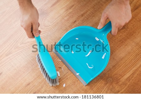 cleaning and home concept - close up of male brooming wooden floor with small whisk broom and dustpan - stock photo
