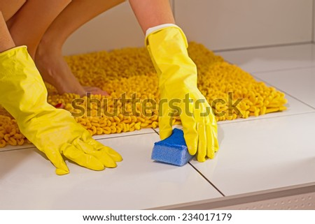 cleaning  bathroom in yellow gloves - stock photo