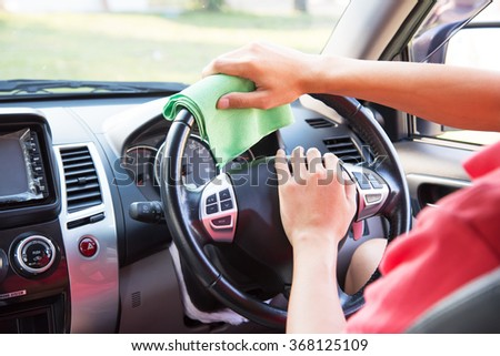 Cleaning car steering wheel with green microfiber cloth - stock photo
