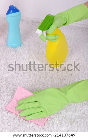 Cleaning carpet with cloth and  sprayer close up - stock photo