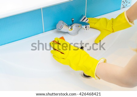 Cleaning - cleaning bathroom sink and faucet with detergent in yellow rubber gloves with orange sponge - housework, spring cleaning concept - stock photo