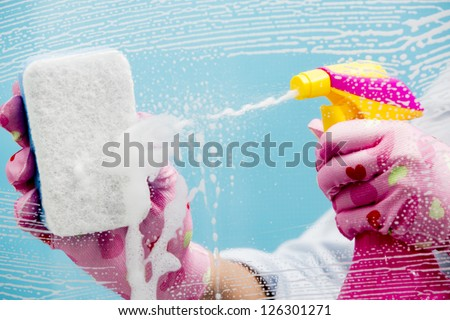 Cleaning - cleaning window pane with spray detergent, spring cleaning concept - stock photo