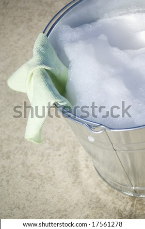 Cleaning cloth and brush in bucket of soapy water - stock photo
