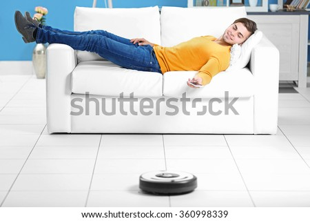 Cleaning concept - automatic robotic hoover clean the room while man relaxing, close up - stock photo