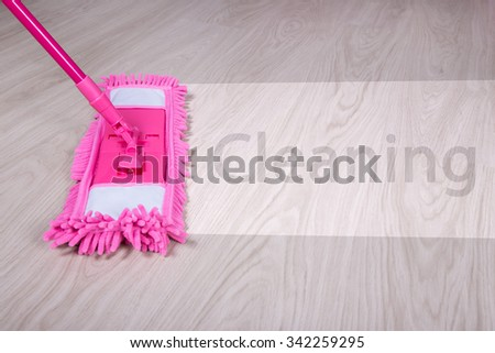cleaning concept - close up of wet mop on wooden floor with word cleaning - stock photo