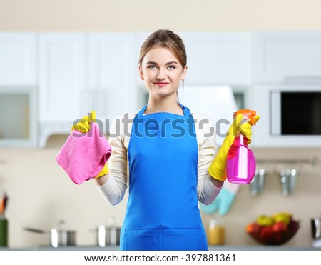 Cleaning concept. Portrait of young woman with washing fluid and rag against kitchen background - stock photo