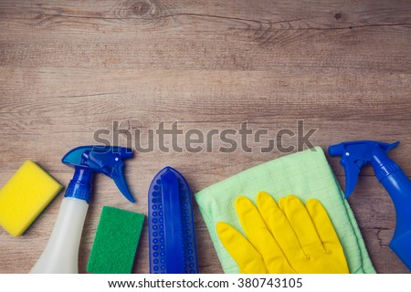 Cleaning concept with supplies on wooden background. View from above - stock photo
