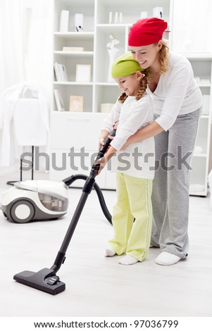 Cleaning day in the family - using a vacuum cleaner - stock photo