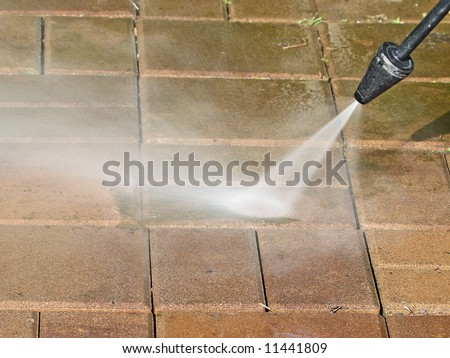 cleaning dirty patio with pressure washer - stock photo